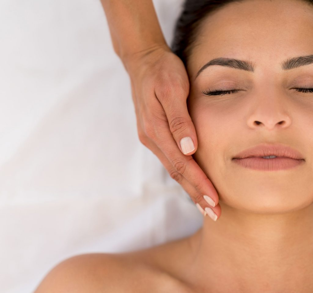 Portrait of a beautiful woman getting a face massage at teh spa - wellness concepts